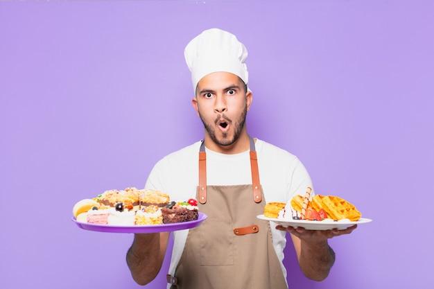Erschrockener ausdruck des jungen hispanischen mannes koch mit waffelkonzept