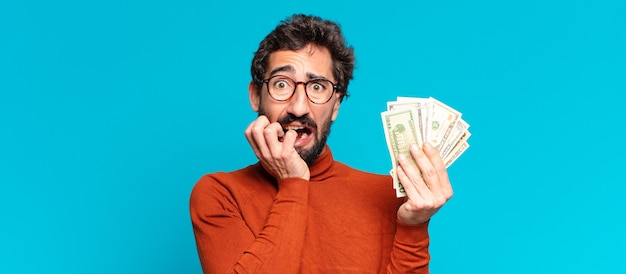 Erschrockener ausdruck des jungen verrückten bärtigen mannes dollar-banknoten-konzept
