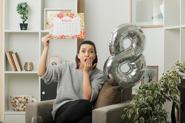 Erschrockener bedeckter mund mit der hand schöne frau am glücklichen frauentag, der den kalender hält, der auf einem sessel im wohnzimmer sitzt