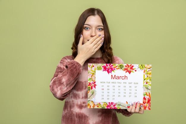 Erschrockener bedeckter mund mit hand schönes junges mädchen am glücklichen frauentag, der kalender hält