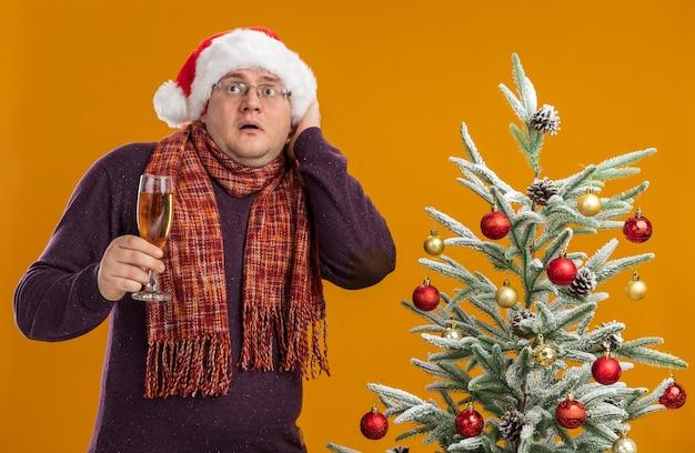 Erschrockener erwachsener mann, der brille und weihnachtsmütze mit schal um hals trägt