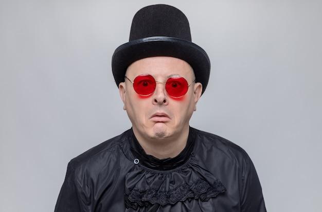 Erschrockener erwachsener slawischer mann mit zylinder und sonnenbrille im schwarzen gothic-hemd