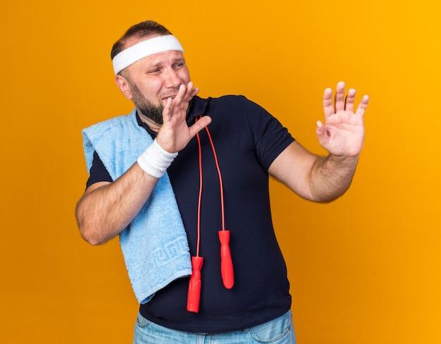 Erschrockener erwachsener slawischer sportlicher mann mit springseil um den hals, der ein stirnband und armbänder trägt, das handtuch auf der schulter hält und die hände offen hält und auf die orange wand mit kopienraum blickt
