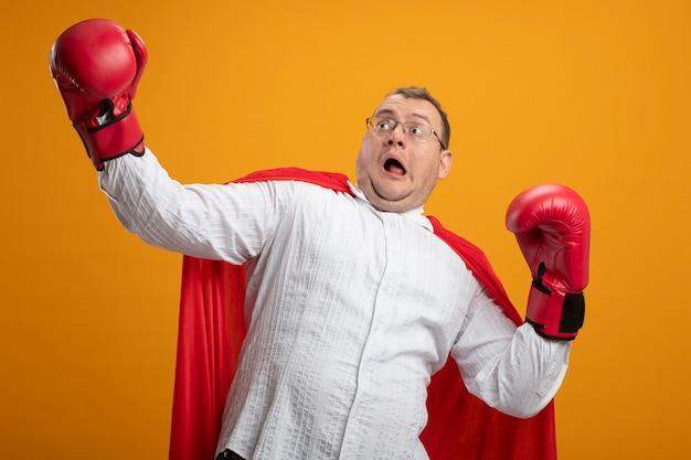 Erschrockener erwachsener slawischer superheldenmann im roten umhang, der brille und kastenhandschuhe trägt, die seite betrachten, die hände in der luft lokalisiert auf orange hintergrund hält
