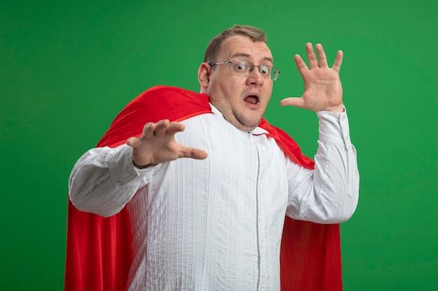Erschrockener erwachsener slawischer superheldenmann im roten umhang, der brillen trägt, die hände in der luft halten kamera betrachten, die auf grünem hintergrund lokalisiert wird