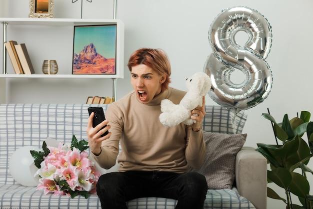Erschrockener, gutaussehender kerl am glücklichen frauentag, der einen teddybären hält, der auf das telefon in seiner hand schaut, das auf dem sofa im wohnzimmer sitzt