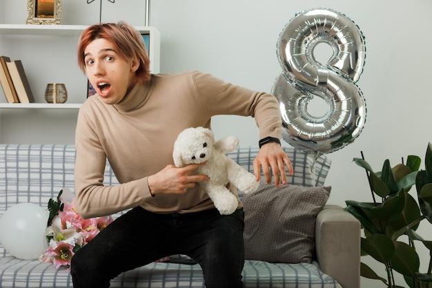 Erschrockener, gutaussehender kerl am glücklichen frauentag, der einen teddybären hält, der auf dem sofa im wohnzimmer sitzt