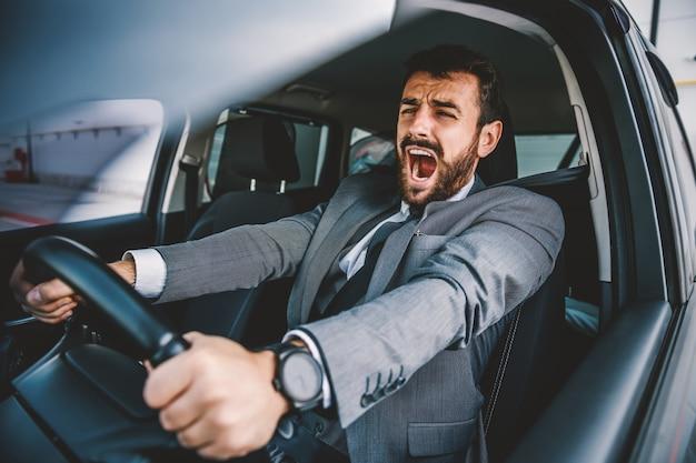 Erschrockener hübscher kaukasischer geschäftsmann, der schreit, während er im auto sitzt und autounfall hat.
