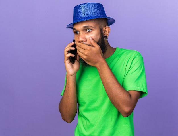 Erschrockener junger afroamerikaner mit partyhut spricht am telefon bedeckten mund mit der hand