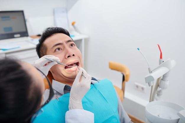 Erschrockener junger asiatischer mann, der ein lustiges gesicht macht, wenn seine zähne in der klinik behandelt werden?