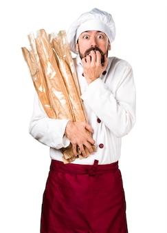 Erschrockener junger bäcker, der etwas brot hält