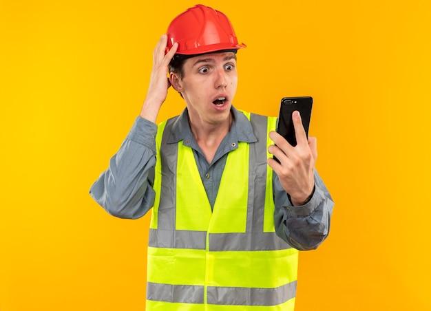Erschrockener junger baumeister in uniform, der das telefon hält und anschaut und die hand auf den kopf legt, isoliert auf gelber wand