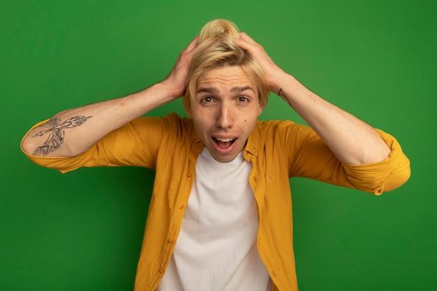 Erschrockener junger blonder kerl, der gelbes t-shirt trägt, packte kopf isoliert auf grün