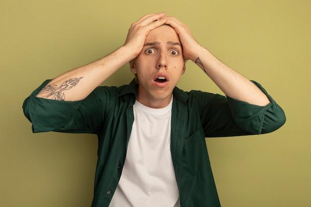 Erschrockener junger blonder kerl, der grünes t-shirt trägt, packte den kopf
