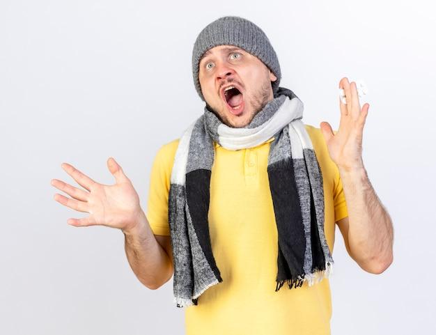 Erschrockener junger blonder kranker slawischer mann, der wintermütze und schal trägt, steht mit erhobenen händen isoliert auf weißer wand mit kopienraum