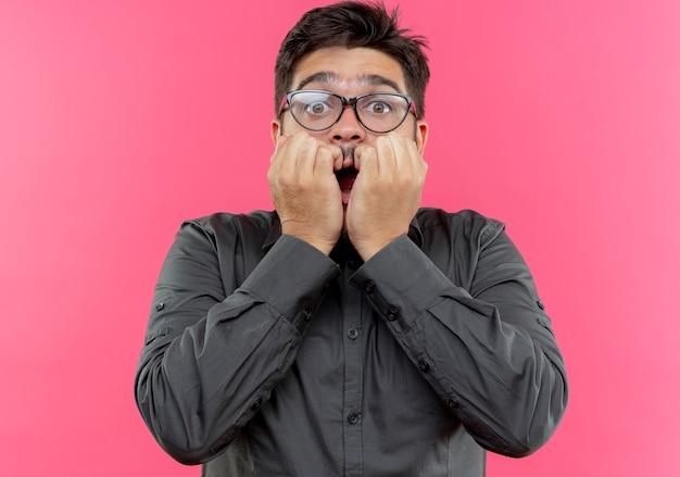 Erschrockener junger geschäftsmann, der brille bedeckt mund mit faust lokalisiert auf rosa wand trägt