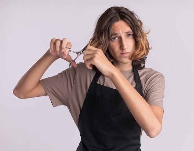 Erschrockener junger gutaussehender friseur in uniform, der sich mit einer schere die haare schneidet