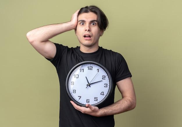 Erschrockener junger gutaussehender kerl, der ein schwarzes t-shirt trägt und eine wanduhr hält, packte den kopf isoliert auf olivgrüner wand?