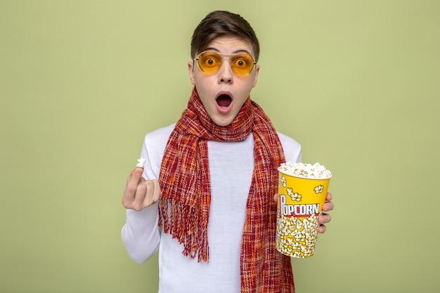 Erschrockener junger gutaussehender kerl mit schal mit brille, der popcorn-eimer hält