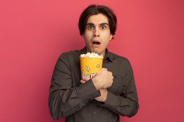 Erschrockener junger gutaussehender kerl mit schwarzem t-shirt umarmte eimer popcorn isoliert auf rosa wand