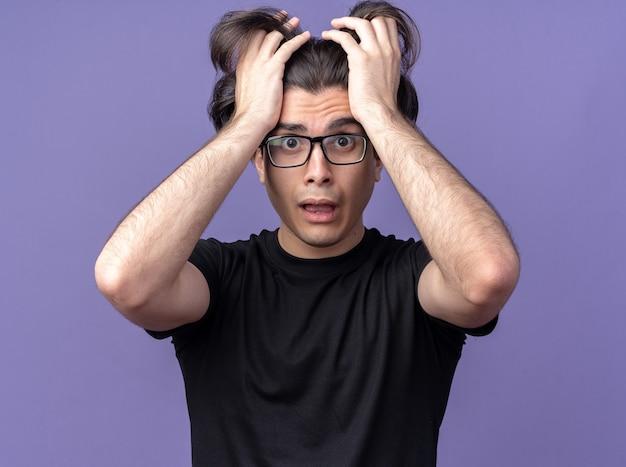 Erschrockener junger gutaussehender kerl mit schwarzem t-shirt und brille packte haare isoliert auf lila wand purple