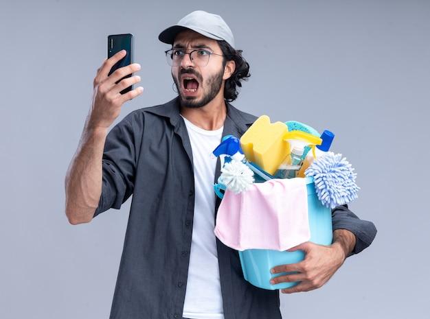 Erschrockener junger gutaussehender putzmann mit t-shirt und mütze, der einen eimer mit reinigungswerkzeugen hält und das telefon in seiner hand isoliert auf weißer wand betrachtet