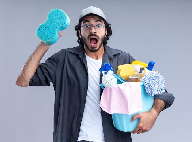 Erschrockener junger gutaussehender putzmann mit t-shirt und mütze mit eimer mit reinigungswerkzeugen und schwamm isoliert auf weißer wand