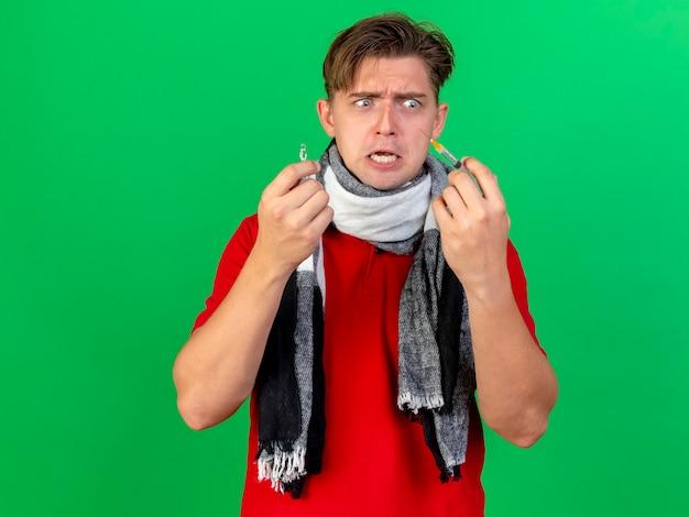 Erschrockener junger hübscher blonder kranker mann, der schal hält spritze und medizinische ampulle betrachtet spritze lokalisiert auf grünem hintergrund mit kopienraum