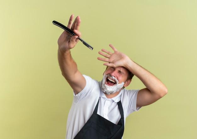 Erschrockener junger hübscher friseur, der uniform trägt, streckt rasiermesser nach vorne aus und legt hand auf die stirn mit rasierschaum auf gesicht isoliert auf grüner wand