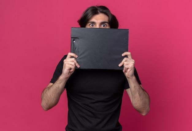 Erschrockener junger hübscher kerl, der das schwarze t-shirt bedeckte gesicht mit zwischenablage um gesicht lokalisiert auf rosa wand trägt