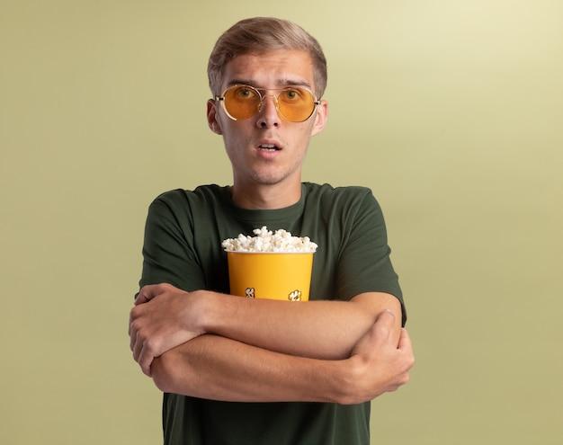 Erschrockener junger hübscher kerl, der grünes hemd mit brille umarmte eimer popcorn, der auf olivgrüner wand isoliert umarmt