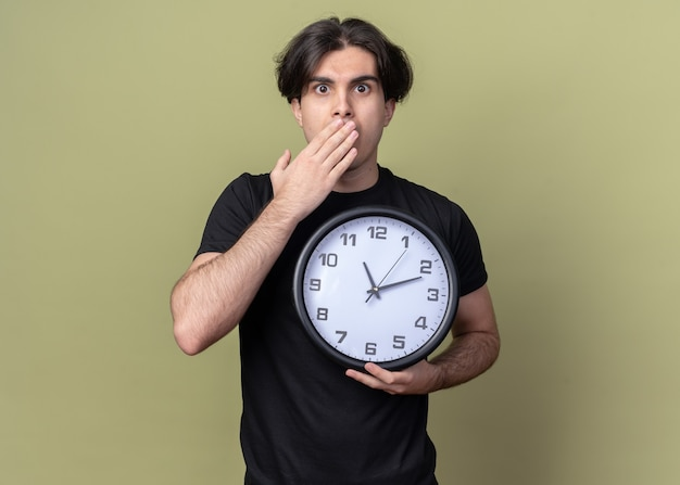Erschrockener junger hübscher kerl, der schwarzes t-shirt trägt, das wanduhr und bedeckten mund mit hand lokalisiert auf olivgrüner wand hält