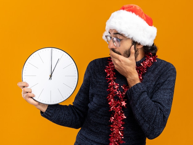 Erschrockener junger hübscher kerl, der weihnachtshut mit girlande am hals hält und den wanduhr bedeckten mund mit der hand lokalisiert auf orange hintergrund trägt