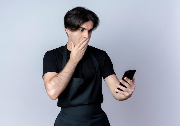 Erschrockener junger hübscher männlicher friseur in der uniform, die telefon bedeckten mund mit hand auf weiß hält und betrachtet