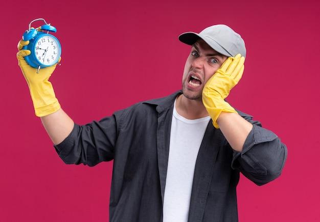 Erschrockener junger hübscher reinigungsmann, der t-shirt und kappe mit handschuhen hält, die wecker halten, der hand auf kopf lokalisiert auf rosa wand setzt