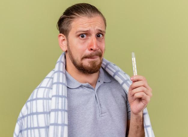 Erschrockener junger hübscher slawischer kranker mann, eingewickelt in kariertes haltethermometer, das kamera lokalisiert auf olivgrünem hintergrund betrachtet