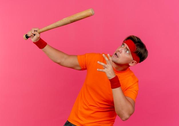 Erschrockener junger hübscher sportlicher mann, der stirnband und armbänder hält, die baseballschläger halten hand auf luft halten und lokalisiert auf rosa wand suchen