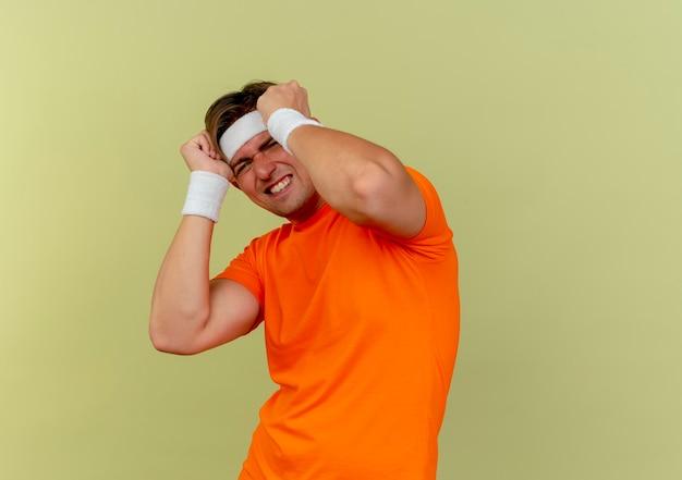 Erschrockener junger hübscher sportlicher mann, der stirnband und armbänder trägt, die hände auf kopf lokalisiert auf olivgrüner wand setzen