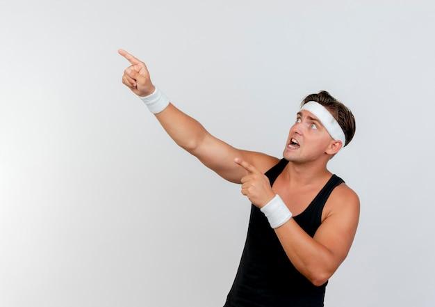 Erschrockener junger hübscher sportlicher mann, der stirnband und armbänder trägt und zur seite zeigt, die auf weißer wand lokalisiert wird