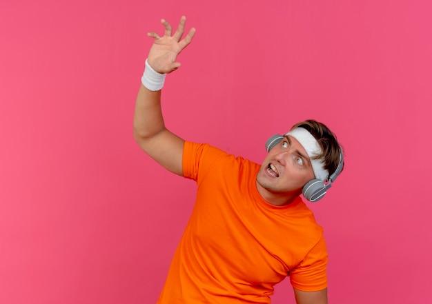 Erschrockener junger hübscher sportlicher mann, der stirnband und armbänder und kopfhörer trägt, die hand heben und lokalisiert auf rosa wand suchen