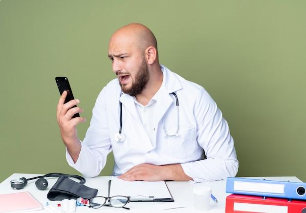 Erschrockener junger kahlköpfiger männlicher arzt, der medizinische robe und stethoskop trägt, die an der schreibtischarbeit sitzen