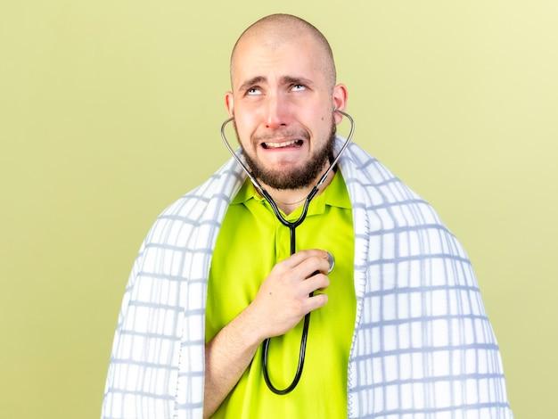 Erschrockener junger kaukasischer kranker mann, eingewickelt in kariertes tragen und halten des stethoskops, das lokalisiert auf olivgrüner wand mit kopienraum schaut