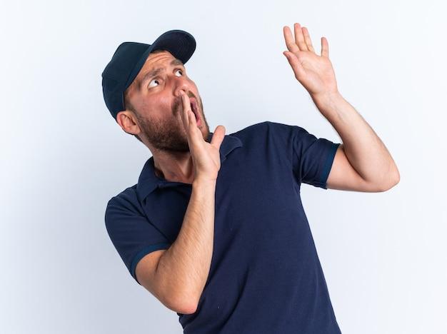 Erschrockener junger kaukasischer lieferbote in blauer uniform und mütze, der nach oben schaut und leere hände zeigt