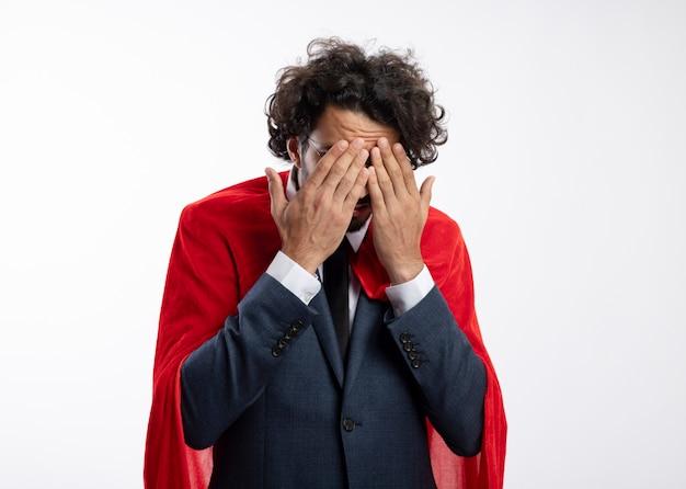 Erschrockener junger kaukasischer superheldenmann in optischer brille, der anzug mit rotem umhang trägt, bedeckt das gesicht mit den händen