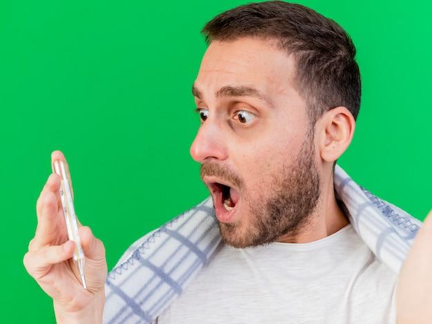 Erschrockener junger kranker mann, der kamera hält, die im karierten halten und im betrachten des thermometers lokalisiert auf grün eingewickelt ist