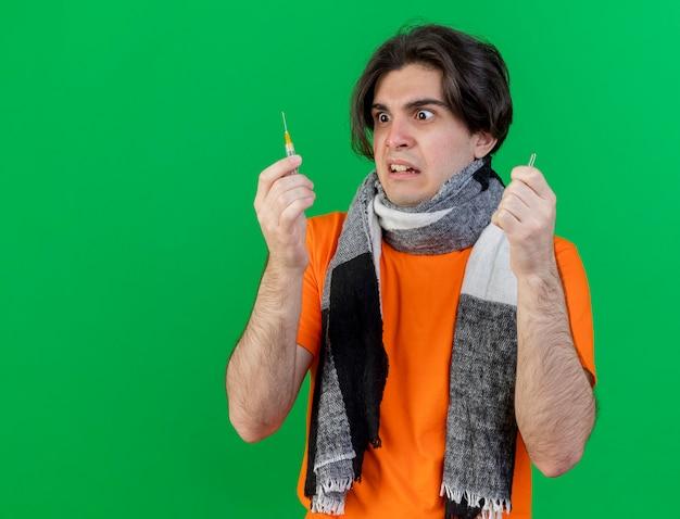 Erschrockener junger kranker mann, der schal hält ampulle trägt und spritze in seiner hand lokalisiert auf grün betrachtet