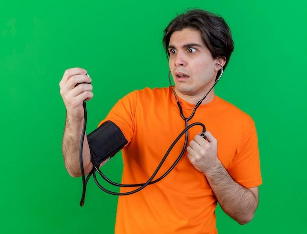 Erschrockener junger kranker mann, der seinen eigenen druck mit dem auf grün isolierten blutdruckmessgerät misst