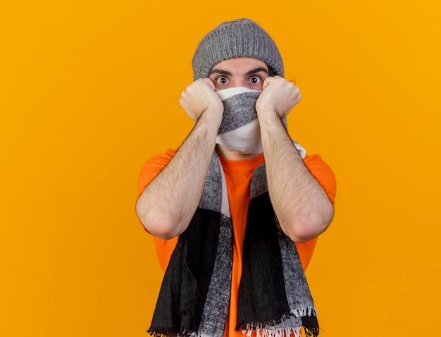 Erschrockener junger kranker mann, der wintermütze mit schal bedeckt gesicht mit schal lokalisiert auf orange hintergrund trägt