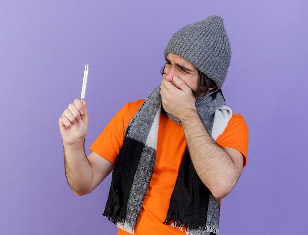 Erschrockener junger kranker mann, der wintermütze mit schal hält und thermometer und bedeckten mund mit hand lokalisiert auf purpur hält