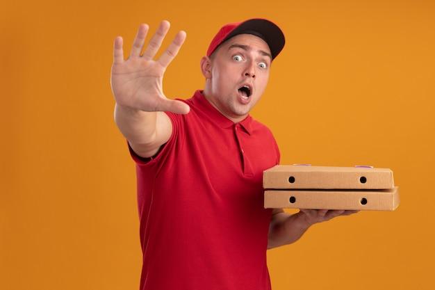 Erschrockener junger lieferbote, der uniform mit kappe hält, die pizzakästen hält, die stoppgeste zeigen, die auf orange wand lokalisiert wird